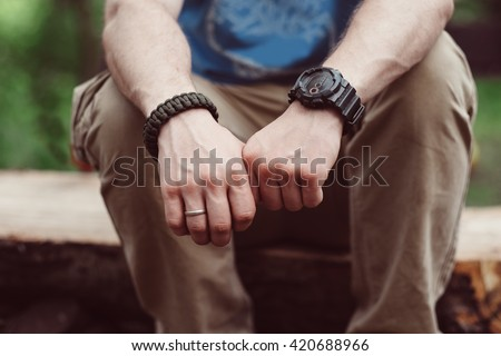 Hunter man hands with survival bracelet and watch. Unrecognizable lumberjack man sitting on wood in the forest. Close-up man hands outdoors. - stock photo