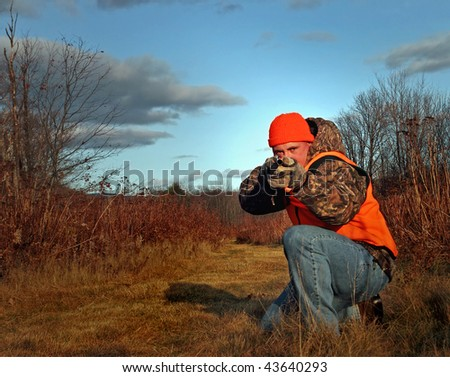 Hunter taking aim with shotgun - stock photo