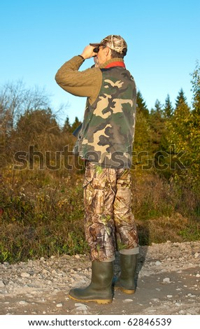 Hunter watching for animals with binoculars. See more my hunting related photos: http://www.shutterstock.com/sets/46993-hunting.html?rid=522649 - stock photo