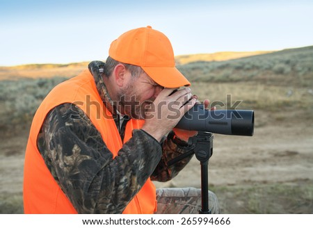 hunter wearing orange and looking through spotting scope - stock photo