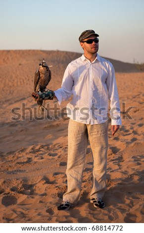 Hunter with a falcon in the desert.