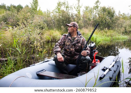 hunter with a gun in the boat - stock photo