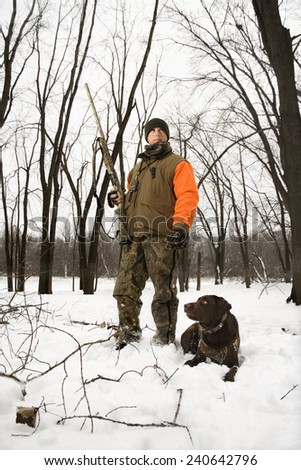Hunter with Chocolate Lab in Snow - stock photo