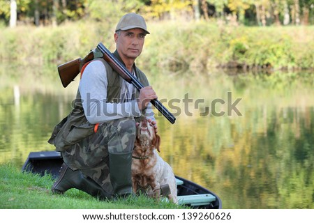 Hunter with dog crouched - stock photo