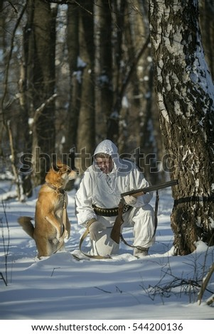 Hunter with dog in the winter forest.