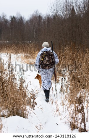 hunter with gun shooting on the snowy field - stock photo