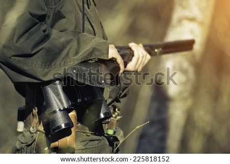 Hunter with his rifle in spring forest, hunter holding a rifle and waiting for prey, hunter shooting  - stock photo