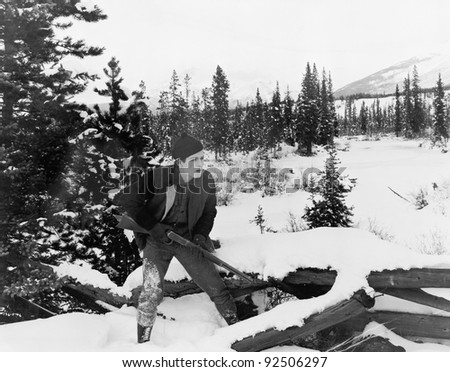Hunter with his rifle walking through  snow covered countryside - stock photo