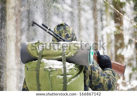 Hunter with optical rifle in winter in snowfall - stock photo