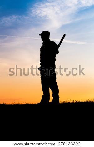 Hunter with shotgun in sunset - stock photo