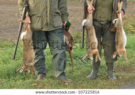 Hunters with Catch: Hare, Duck and Pheasant in hand - stock photo