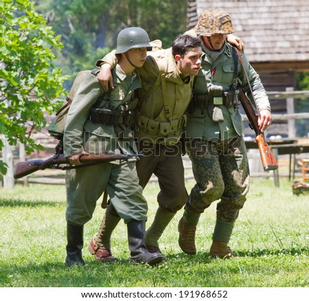HUNTERSVILLE, NC - MAY 3, 2014:  Military reenactors  in German and American uniforms recreate a World War II battle at Historic Latta Plantation in commemoration of the 70th anniversary of D-Day. - stock photo