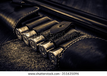 Hunting ammunition 12 gauge in leather bandolier and double-barreled shotgun on a wooden table. Focus on the cartridges, image vignetting and the yellow toning - stock photo