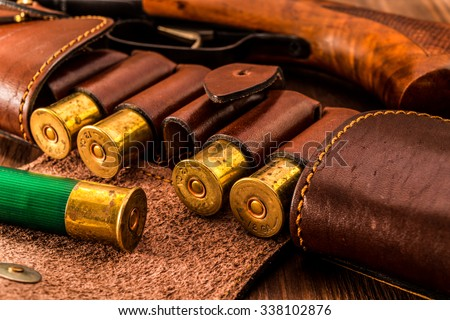 Hunting ammunition 12 gauge in leather bandolier and shotgun on a wooden table. Focus on the cartridges - stock photo