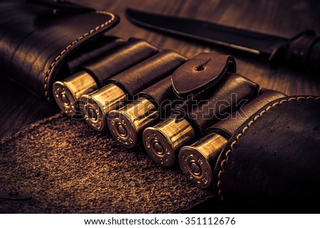 Hunting ammunition 12 gauge in leather bandolier with combat knife on a wooden table. Focus on the cartridges, image vignetting and the yellow-blue toning - stock photo