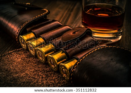 Hunting ammunition 12 gauge in leather bandolier with glass of whiskey on a wooden table. Focus on the cartridges, image vignetting and the orange-blue toning - stock photo