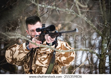 Hunting, army, military concept - sniper holding rifle and aiming at target in the forest during operation - stock photo