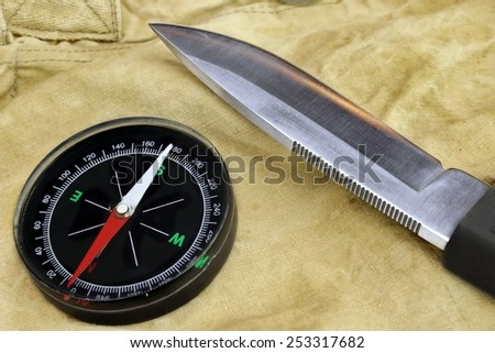 Hunting Knife with Rubberized  Handle and Compass on the Camouflage Baggy Background - stock photo
