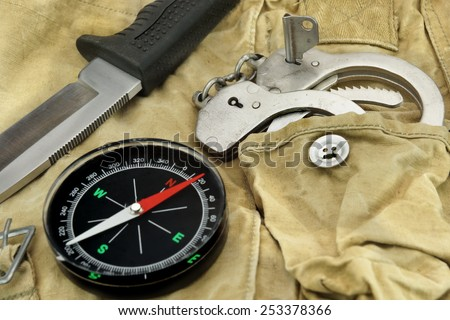 Hunting Knife with Rubberized  Handle, Compass and  Handcuffs on the Camouflage Baggy Background - stock photo