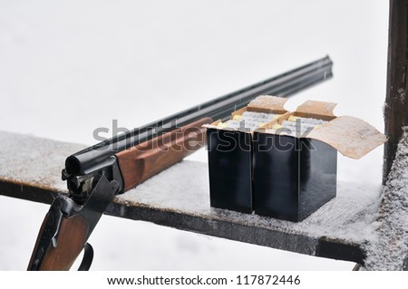 Hunting rifle and bullets. On winter background. - stock photo