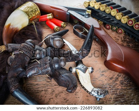 hunting rifle and dagger and amulet on the table - stock photo