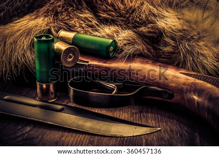 Hunting rifle with combat knife and cartridges lying next to the animal's fur produced. View close-up, image vignetting and the yellow-blue toning - stock photo