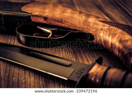 Hunting rifle with combat knife lying on a wooden table. Image vignetting and the yellow-blue toning - stock photo