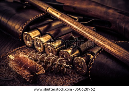 Hunting rifle with leather bandolier and a ramrod with brushes for cleaning weapons lying on a wooden table, image vignetting and the yellow-blue toning