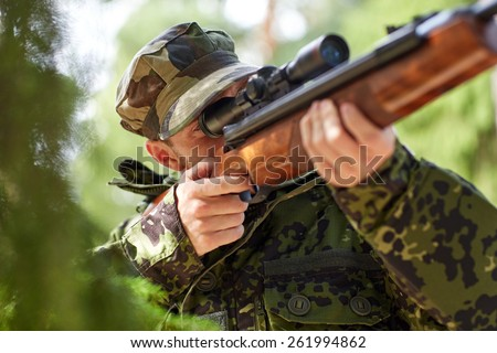 hunting, war, army and people concept - young soldier, ranger or hunter with gun walking in forest - stock photo