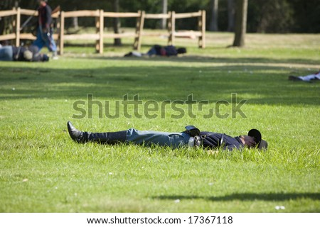 "HUNTINGTON BEACH, CA Aug 30, 2008:  Civil war re-enactors performing a battle at the Huntington Central Park, in Huntington Beach, California.  ""Dead"" soldiers on the field of battle. - stock photo"