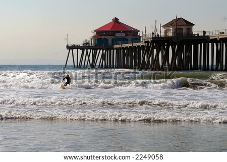 Huntington Beach Pier with surfer in foreground. - stock photo