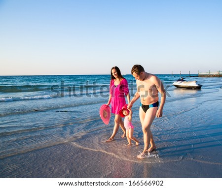 Huppy family on beach in Persian Gulf ,Dubai. Tanning near ocean, tropical resort, summer holiday - stock photo