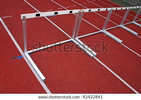 Hurdles and red running tracks in a stadion - stock photo