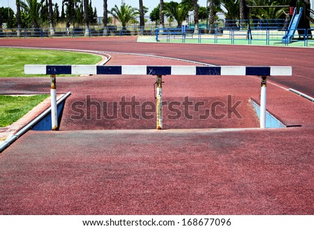 Hurdles on red running tracks - stock photo