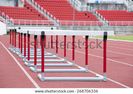 hurdles on the red running track prepared for competition - stock photo