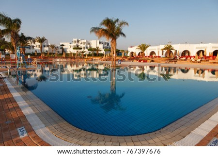 Hurgada, Egypt - 14 August, 2014: Pool on a tropical beach, reflection of palm tree in the water - vacation background