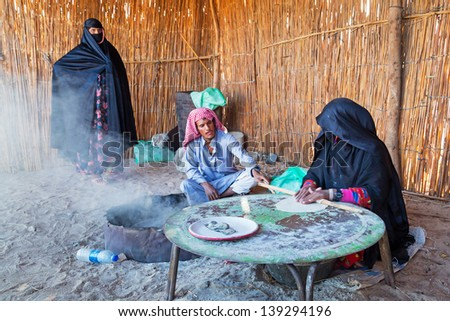 HURGHADA, EGYPT - APR 16, 2013: Unidentified people baking bread in the bedouin village on the desert near Hurghada, April 16, 2013. This Village is one of main tourist attractions on desert in Egypt. - stock photo