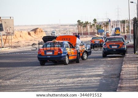 HURGHADA, EGYPT - CIRCA NOV, 2015: Egyptian taxi drivers repair broken car on the road side. The taxi service is in the Egypt - stock photo