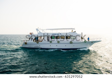 Hurghada, Egypt - February 24, 2017: tourist white ship or yacht, modern motor boat floating on blue sea water on sunny day on clear sky background. Travelling and adventure