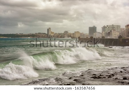 Hurricane in Havana with huge waves hitting the sea wall and a view of the skyline - stock photo