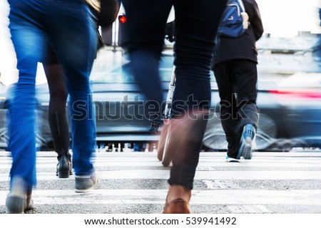 hurried people in motion blur crossing a city street