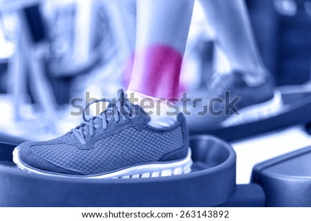 Hurting ankles - pain caused by fitness injury. Closeup of leg with red circle showing painful area of female athlete training on elliptical exercise machine. Sprained ankle concept. - stock photo