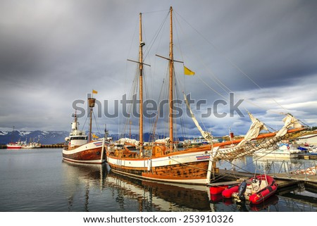 Husavik harbor in Northern Iceland with whale watching boats - stock photo