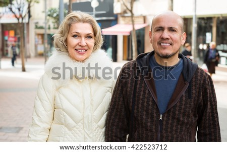 husband and blonde wife having a walk together outdoors - stock photo