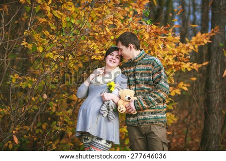 husband and his pregnant wife are walking in the forest, they are holding a teddy bear - stock photo