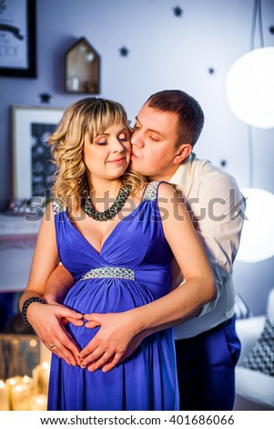 husband and his pregnant wife in a long blue dress resting near the tree in the evening
