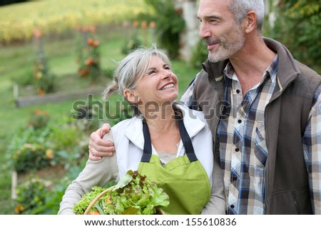 Husband and wife enjoying being in kitchen garden - stock photo