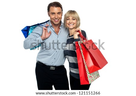 Husband and wife enjoying shopping. Carrying colorful shopping bags. - stock photo