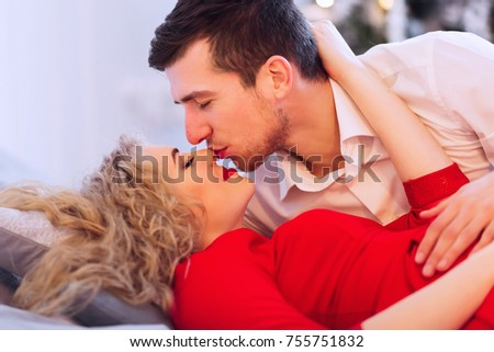 Husband And Wife Gently Kissing On The Bed