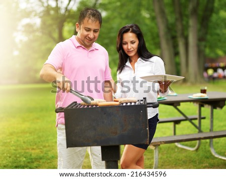 husband and wife grilling food at a park - stock photo